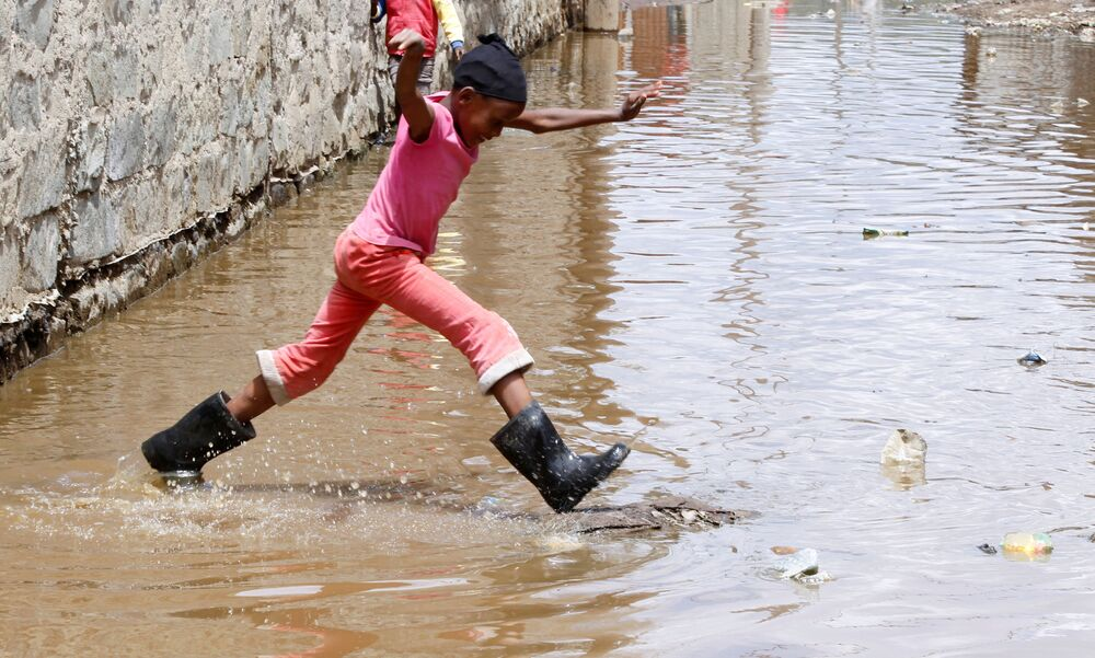 A child jumps as she wades through flood waters after the levels at Lake Naivasha swelled to a record high, pushing hundreds of people from surrounding farms around Naivasha town within Nakuru county, Kenya on 8 November 2020.
