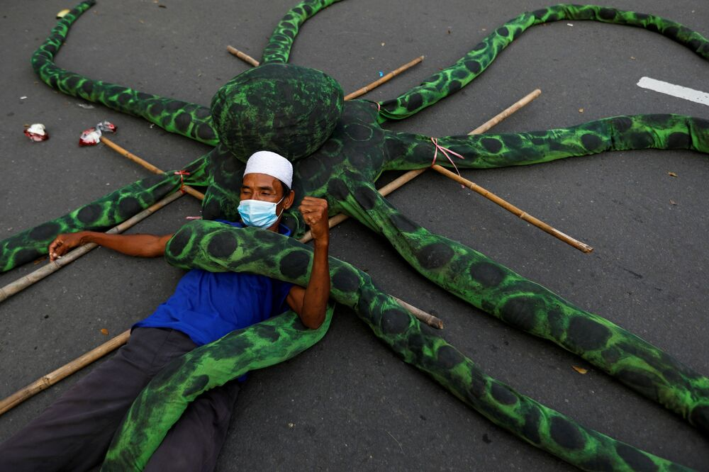 A fisherman wearing a protective mask lies on an artificial octopus during a protest against the government's labour reforms in a job creation Bill in Jakarta, Indonesia, 10 November 2020.