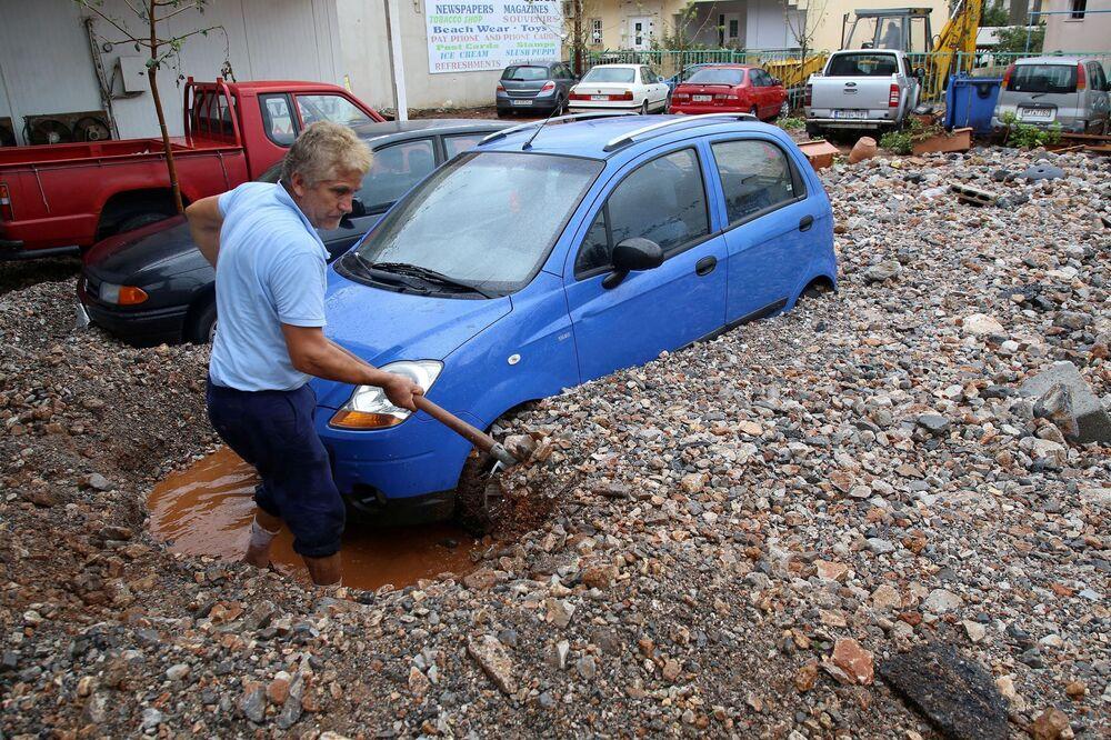 A local shovels mud blocking a car, after heavy rainfall in Malia on the island of Crete, Greece, 10 November 2020.