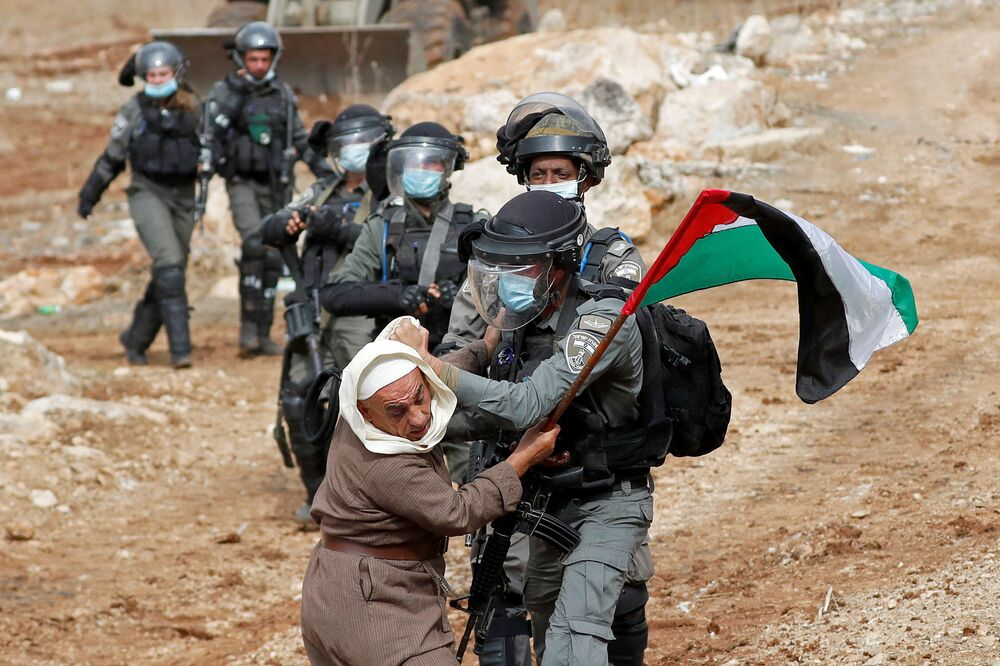 A Palestinian demonstrator scuffles with an Israeli border police member during a protest against  Jewish settlements and US President Donald Trump, in Beit Dajan in the Israeli-occupied West Bank 6 November 2020.