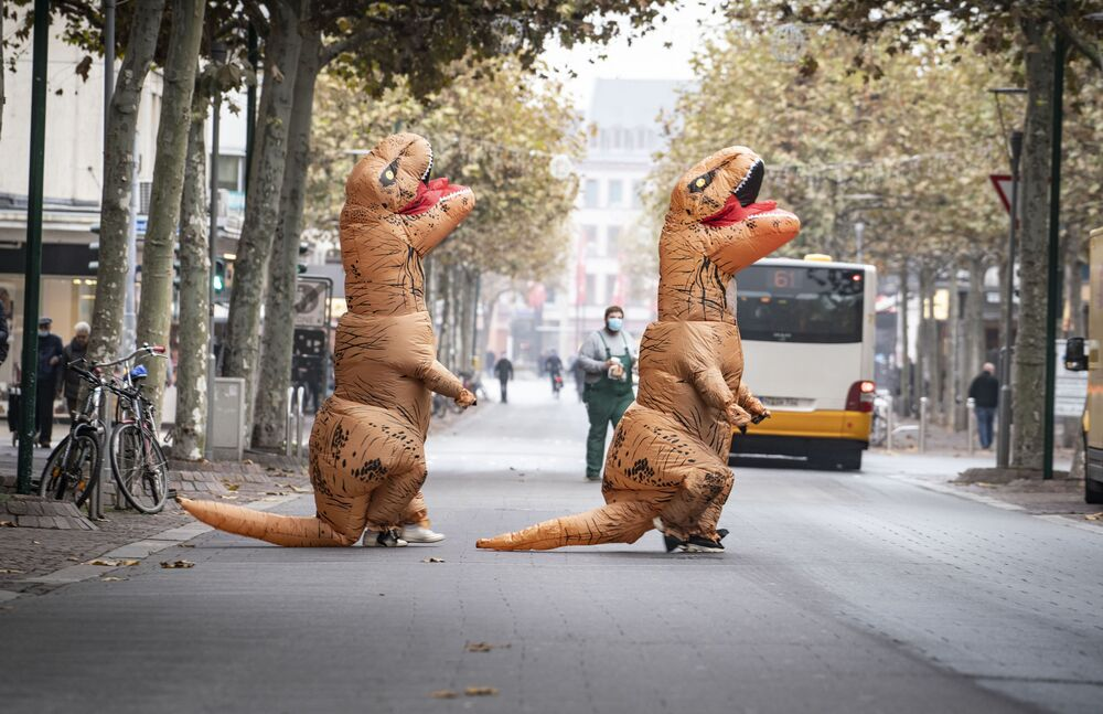 Two carnival-goers in inflatable dinosaur costumes cross a street near the Schillerplatz in Mainz, Germany, 11 November 2020.