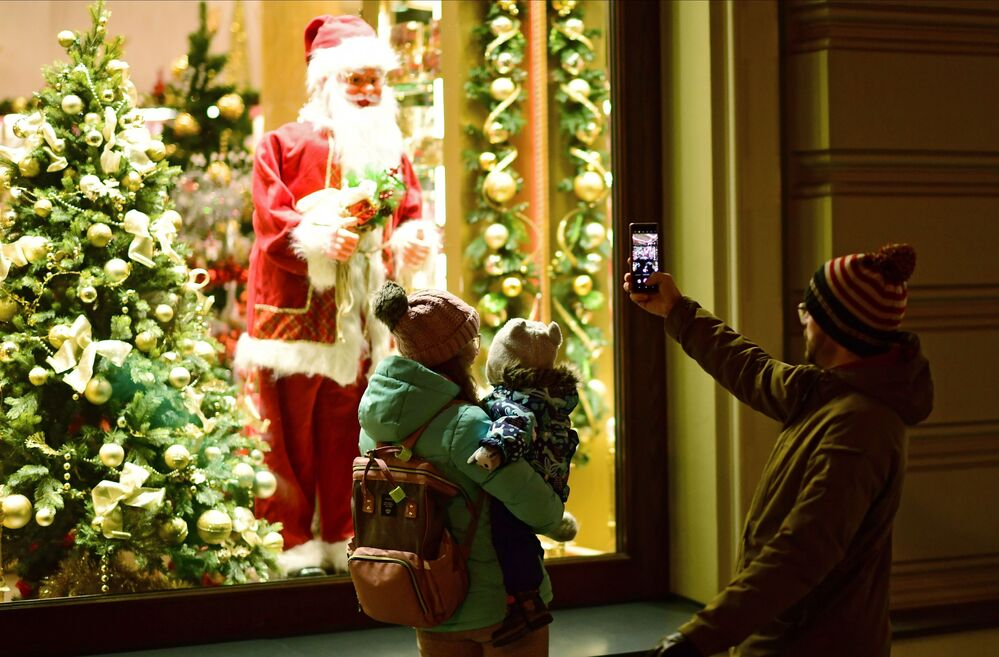 A passer-by takes a picture of Santa Claus in Nikolskaya Street in Moscow.