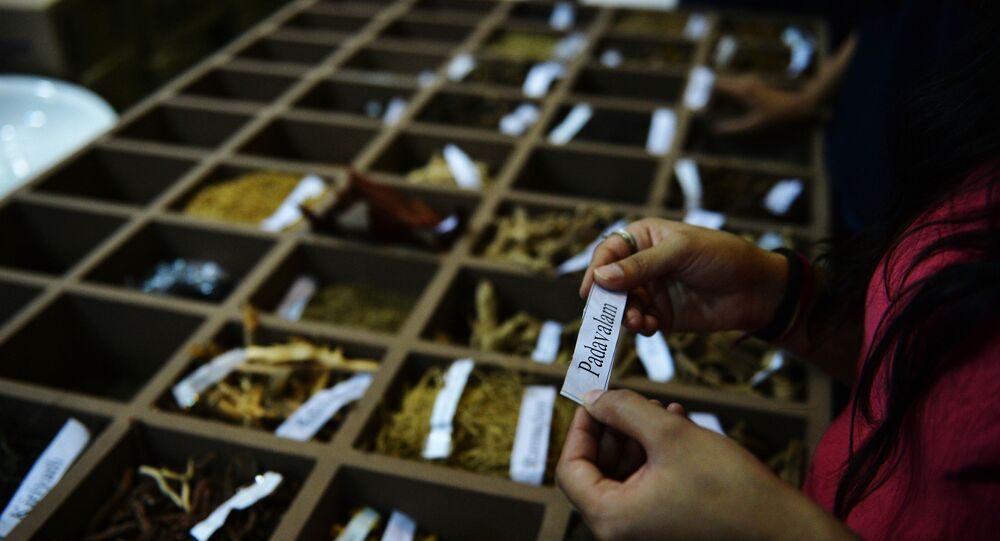 In this photograph taken on November 6, 2014, An Indian visitor reads the name of a herb from a display during the sixth World Ayurveda Congress and Arogya Expo in New Delhi.