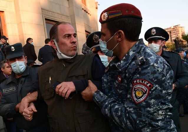 Police detain a participant in an opposition rally in Yerevan