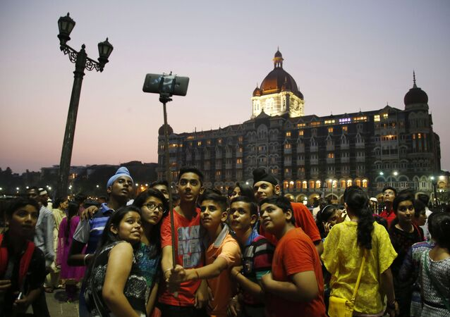 In this photo dated Saturday, 5 December 2015, Indian students take a selfie in front of the Taj Mahal hotel in Mumbai, India.