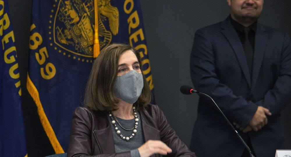 Oregon Gov. Kate Brown attends a news conference Tuesday, Nov. 10, 2020, in Portland, Ore. Brown and Oregon health officials warned Tuesday of the capacity challenges facing hospitals as COVID-19 case counts continue to spike in the state.