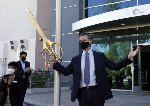 California Gov. Gavin Newsom participates in a ribbon cutting ceremony at a COVID-19 testing facility Friday, Oct. 30, 2020, in Valencia, Calif. Newsom announced the new $120 million, 134,000 sq. foot coronavirus testing facility in Valencia Friday.