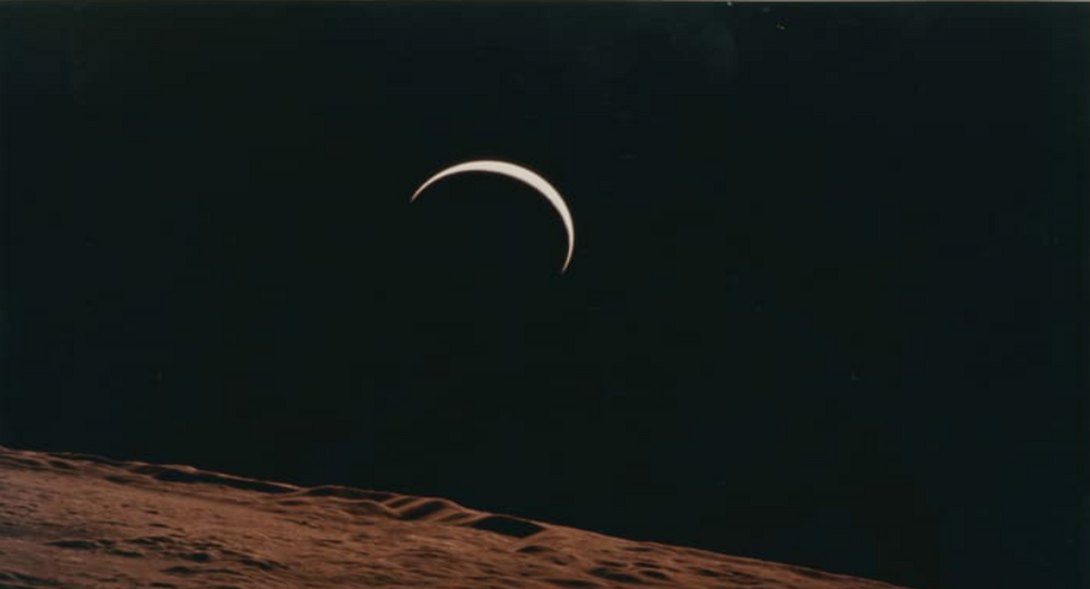Crescent Earth rising beyond the Moon's barren horizon, 1971.