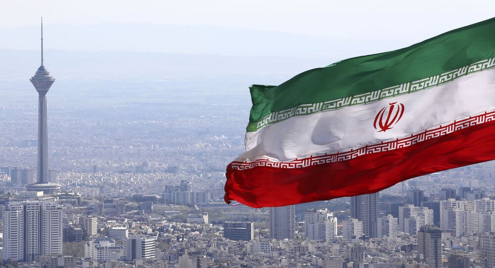 In this 31 March 2020, file photo, Iran's national flag waves as Milad telecommunications tower and buildings are seen in Tehran, Iran