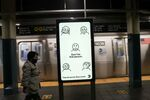 A subway rider wearing a mask passes a city-sponsored ad promoting face masks as a precautionary measure, as the global outbreak of the coronavirus disease (COVID-19) continues, in New York City, U.S., November 14, 2020.