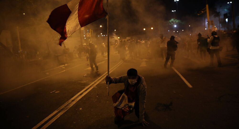 A protester holds a banner with the country's national color as police launch tear gas to disperse protesters who gathered in Plaza San Martin to demonstrate their refusal to recognize Peru's new government, in Lima, Saturday, Nov. 14, 2020.