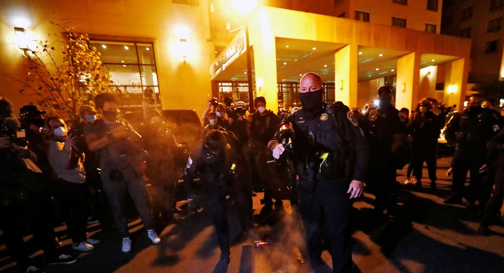 A Washington DC metropolitan police officer stomps out the fire and threatens to pepper spray the protesters after anti-fascist protesters burn a poster of U.S. President Donald Trump at the front door of the Capital Hilton hotel in downtown Washington, U.S. November 14, 2020.