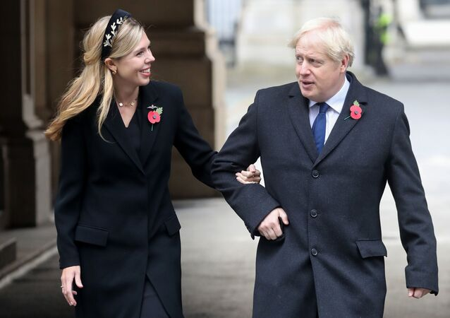 Britain's Prime Minister Boris Johnson (R) and his parter Carrie Symonds (L) meet veterans at the Remembrance Sunday ceremony at the Cenotaph on Whitehall in central London, on November 8, 2020