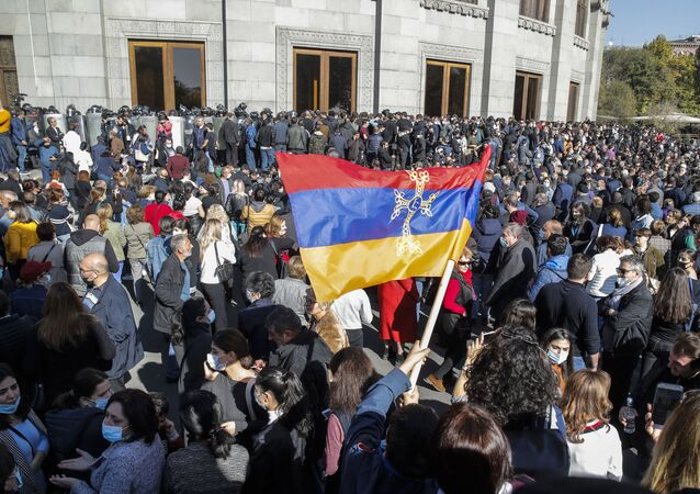 Protesters wave an Armenian national flag during a protest against an agreement to halt fighting over the Nagorno-Karabakh region, in Yerevan, Armenia, Wednesday, Nov. 11, 2020.