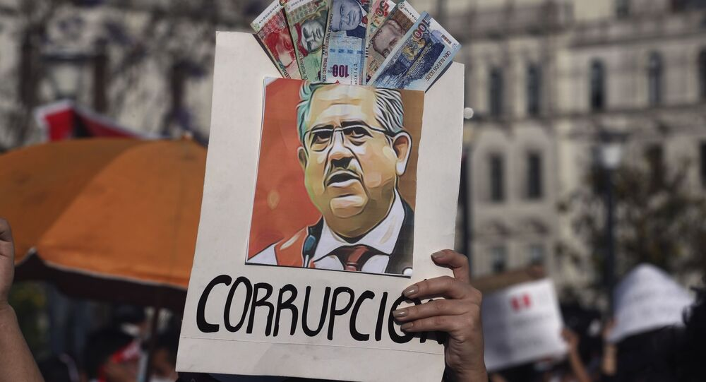 A protester holds up a poster adorned with play money with the Spanish word for corruption and an image depicting Peru's newly sworn-in president Manuel Merino