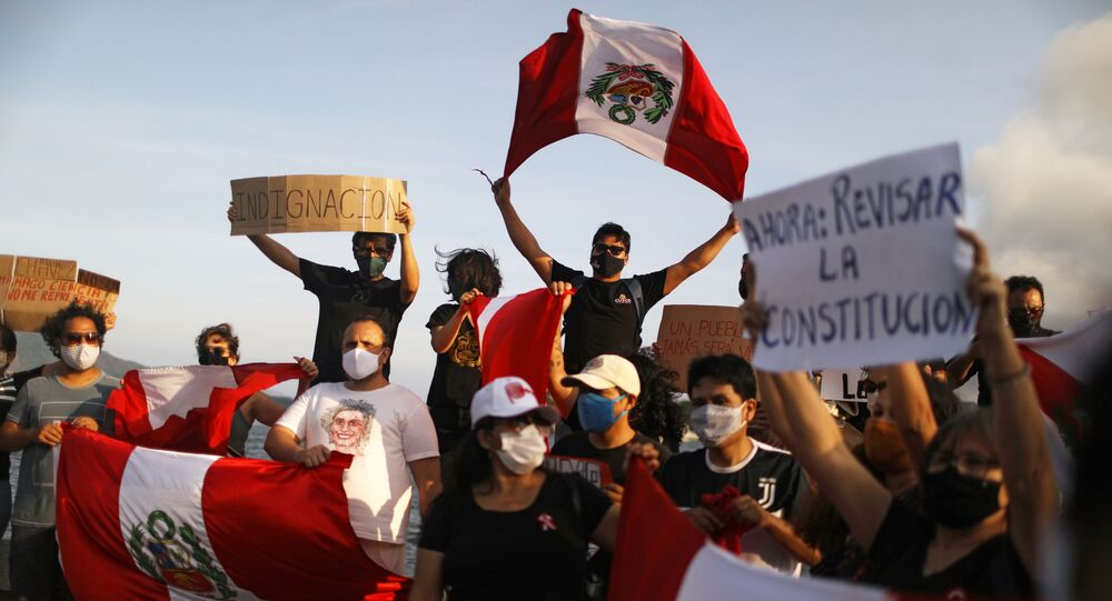 People hold signs and Peruvian flags during a rally after Peru's interim President Manuel Merino resigned, in Rio de Janeiro, Brazil, November 15, 2020.