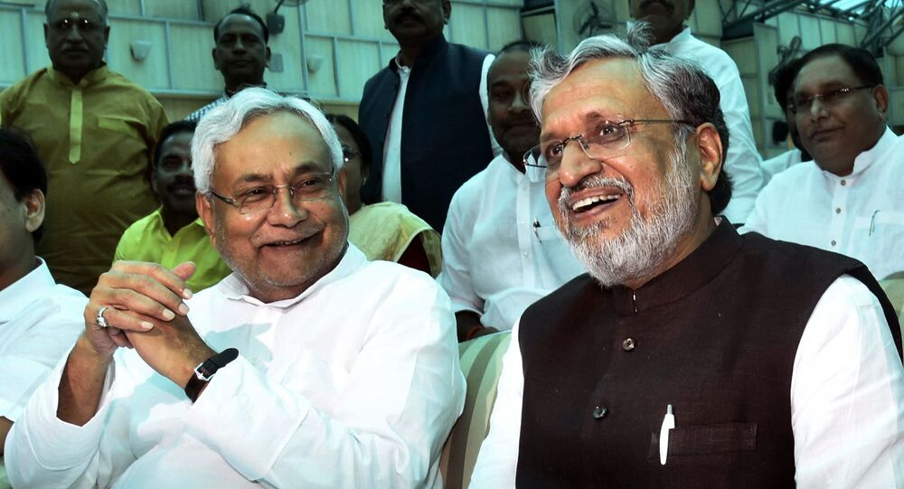 Bihar Chief Minister Nitish Kumar, left, and Deputy Chief Minister Sushil Kumar Modi share a light moment after oath taking ceremony at Raj Bhawan in Patna, India, Thursday, July 27, 2017.