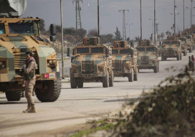 Turkish military convoy drives in Idlib province, Syria, Saturday, Feb. 22, 2020