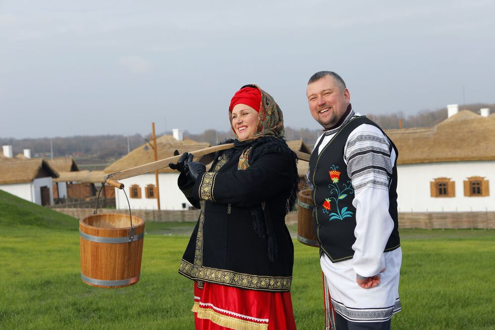 A woman and a man, both dressed in historical costumes, attend the opening of the Slobozhanschina ethno village in the Belgorod Region.
