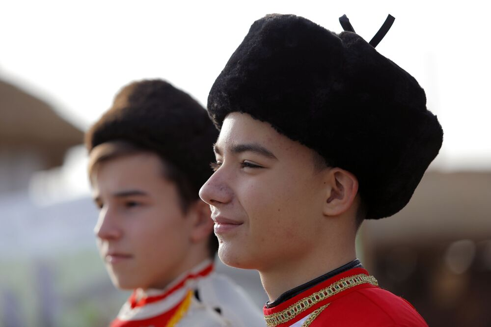 Young men dressed in historical costumes watch the opening of the Slobozhanschina historical and cultural complex in the Belgorod Region.
