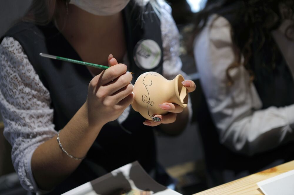 A woman paints on a jug during a master class at the Slobozhanschina historical and cultural complex in the Belgorod Region.