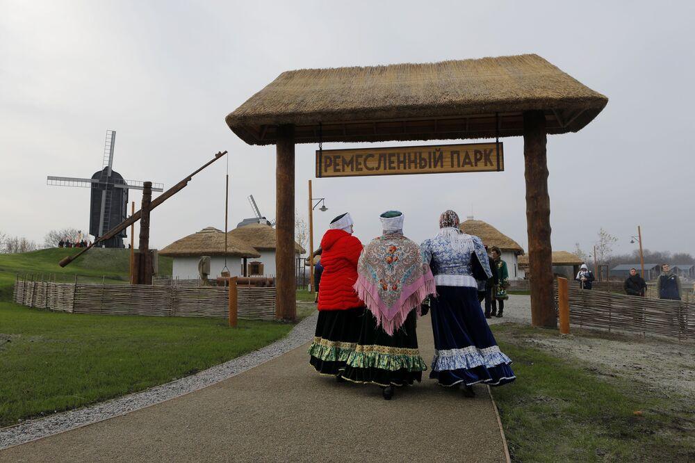 Women dressed in historical costumes walk around the premises of the newly-inaugurated ethno village Slobozhanschina in the Belgorod Region.