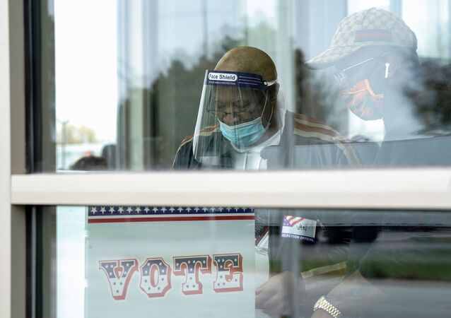 Poll worker Van Paterson assists an early voter with a voting machine inside the Milwaukee Public Library's Good Hope branch, on the first day of in-person voting in Wisconsin, U.S., October 20, 2020.