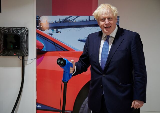 Britain's Prime Minister Boris Johnson holds a charging cable for an electric vehicle (EV), during his visit to the headquarters of energy supplier Octopus Energy in London on October 05, 2020