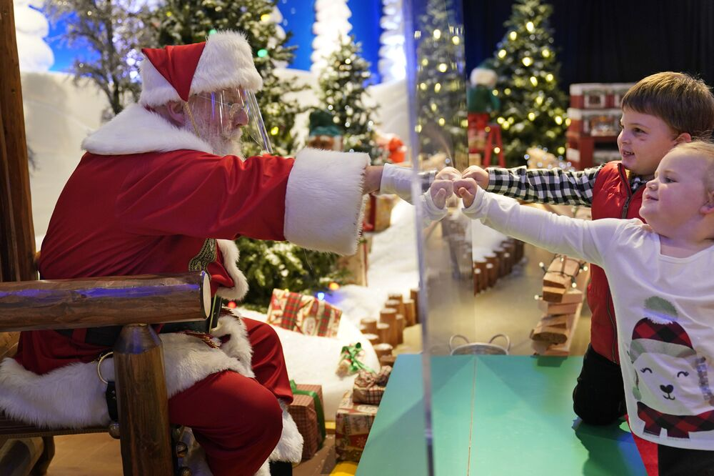Julianna, 3, and Dylan, 5, Lasczak visit Santa through a transparent barrier at a Bass Pro Shop in Bridgeport, Conn., Tuesday, 10 November 2020. Santa Claus is coming to the mall: just don't try to sit on his lap. Malls are doing all they can to keep the jolly old man safe from the coronavirus, including banning kids from sitting on his knee, no matter if they've been naughty or nice.