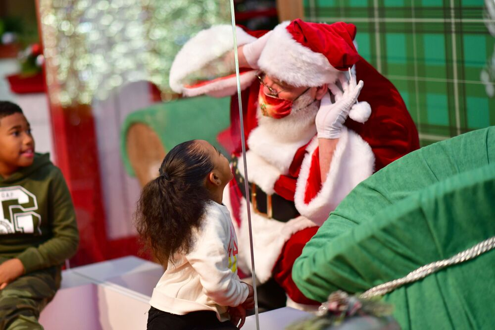 Brother and sister DeShaye, 8, and Shaye'Lah Powell, 4, speak to a man dressed as Santa Claus, who sits behind a plexiglass divider due to the coronavirus disease (COVID-19) pandemic, at the Willow Grove Park Mall in Willow Grove, Pennsylvania, U.S. 14 November 2020. REUTERS/Mark Makela
