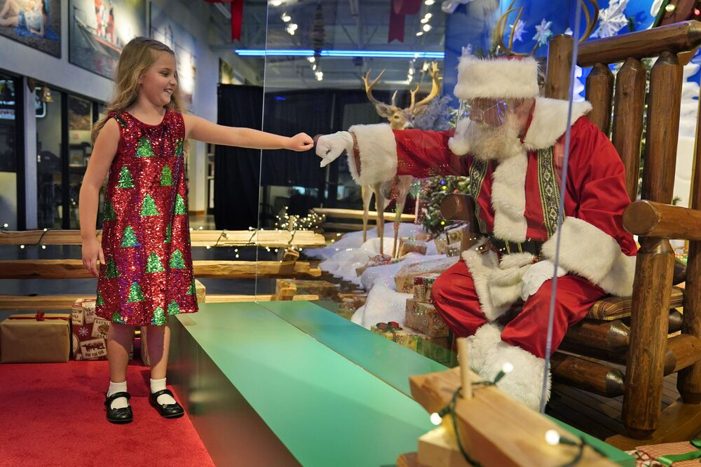 Sydney Poulos, 8, gives Santa a fist bump through a transparent barrier at a Bass Pro Shop in Bridgeport, Conn., Tuesday, 10 November 2020. Santa Claus is coming to the mall: just don't try to sit on his lap. Malls are doing all they can to keep the jolly old man safe from the coronavirus, including banning kids from sitting on his knee, no matter if they've been naughty or nice.