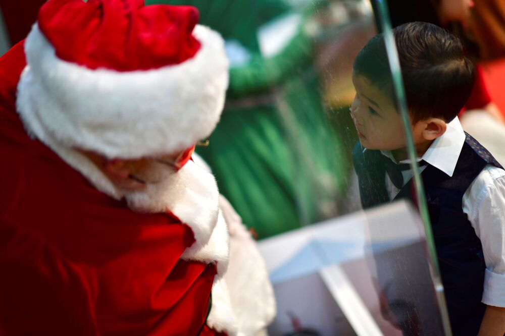 A man dressed as Santa Claus sitting behind a plexiglass barrier due to the coronavirus disease (COVID-19) pandemic speaks with a boy at the Willow Grove Park Mall in Willow Grove, Pennsylvania, US, 14 November 2020. REUTERS/Mark Makela