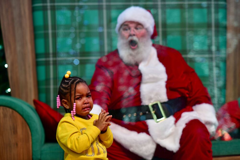 Majesty Davis, 3, cries while visiting a man dressed as Santa Claus, who sits behind a plexiglass divider due to the coronavirus disease (COVID-19) pandemic, at the Willow Grove Park Mall in Willow Grove, Pennsylvania, US, 14 November 2020. REUTERS/Mark Makela