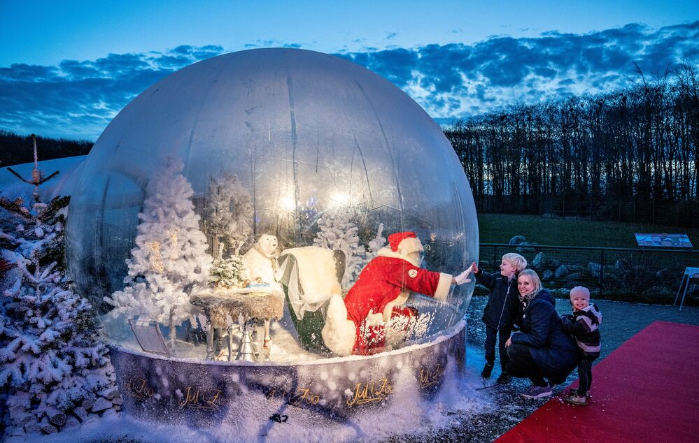 A person dressed as a Santa Claus meets a child while sitting in a Santa Claus bubble as he opens Christmas season at Aalborg Zoo, amid the coronavirus disease (COVID-19) outbreak, in Aalborg, Denmark, 13 November 2020. Ritzau Scanpix/Henning Bagger