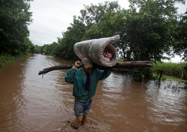 A man carries his belongings through a flooded road after the passing of Storm Iota, in Marcovia, Honduras November 18, 2020.