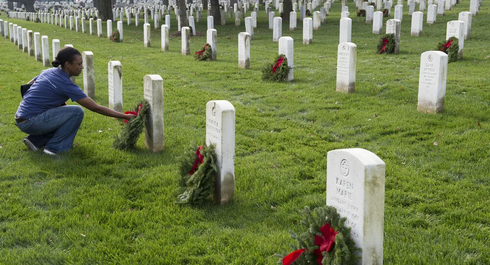 A woman places wreaths at gravesites during the 2015 National Wreaths Across America event at Arlington National Cemetery on December 12, 2015 in Arlington, Virginia