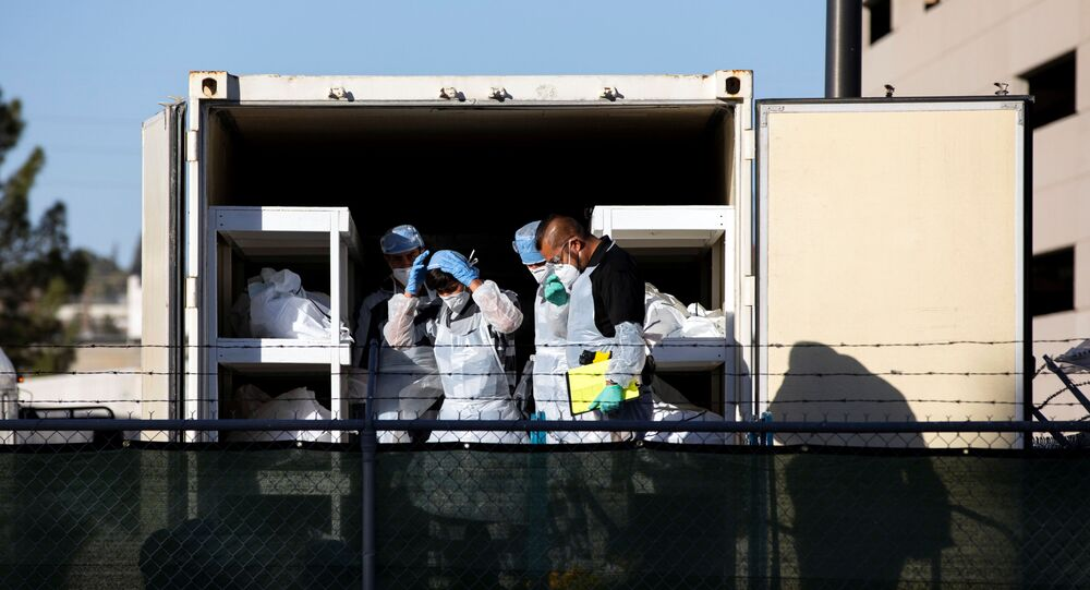 El Paso County detention inmates, also known as ?trustees? (low level inmates) and Sheriff officers and morgue staff help move bodies to refrigerated trailers deployed during a surge of coronavirus disease (COVID-19) deaths, outside the Medical Examiner's Office in El Paso, Texas, U.S. November 14, 2020