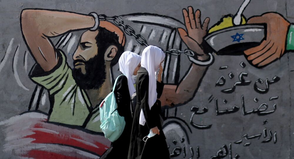 FILE PHOTO: Palestinian students walk past a mural depicting hunger-striking Palestinian prisoner Maher Al-Akhras, who is held by Israel, in the central Gaza Strip, 19 October 2020
