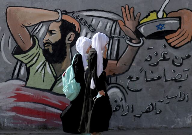 FILE PHOTO: Palestinian students walk past a mural depicting hunger-striking Palestinian prisoner Maher Al-Akhras, who is held by Israel, in the central Gaza Strip October 19, 2020