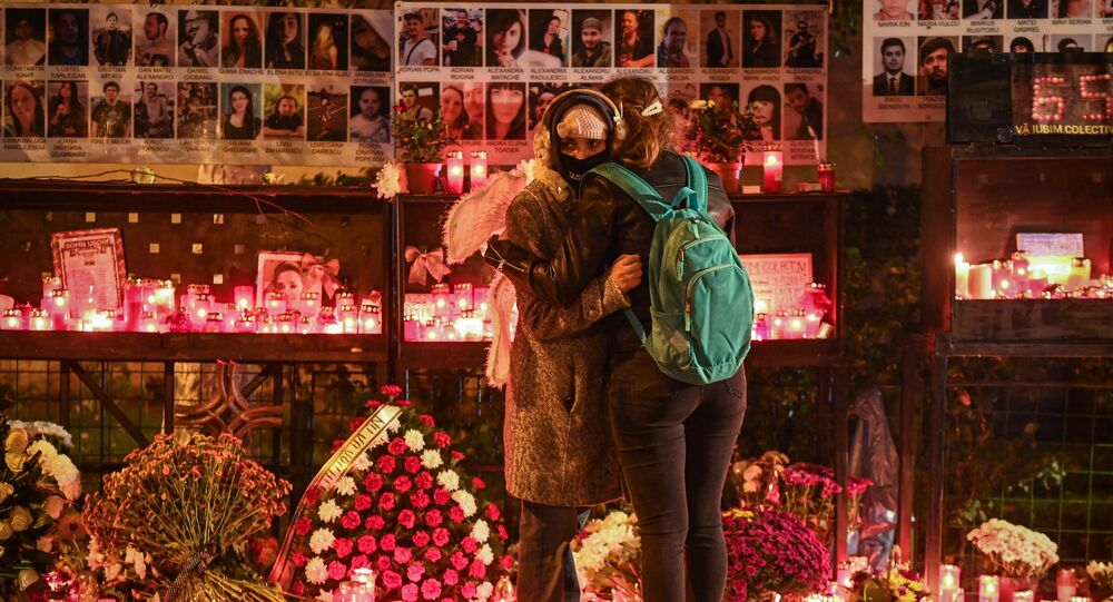Two young women embrace next to a candlelight tribute to those who died in the fire at the Colectiv nightclub in Bucharest in 2015.
