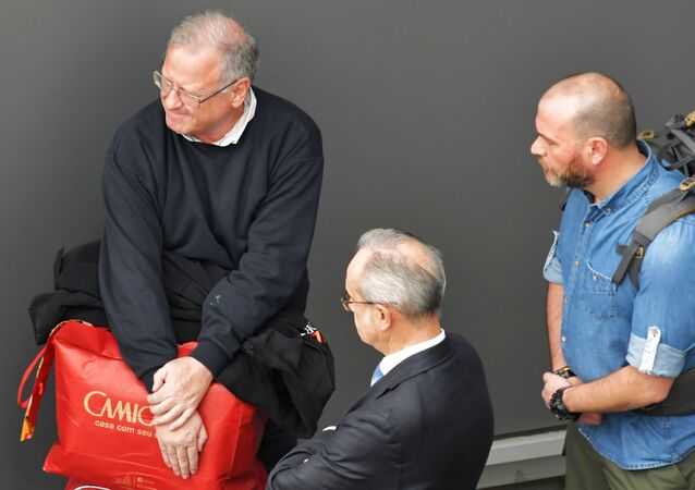Spaniard Carlos Garcia Julia (L) awaits transport at Gaurulhos International Airport, in Sao Paulo, Brazil, to a plane to be extradited to Spain, on February 6, 2020.