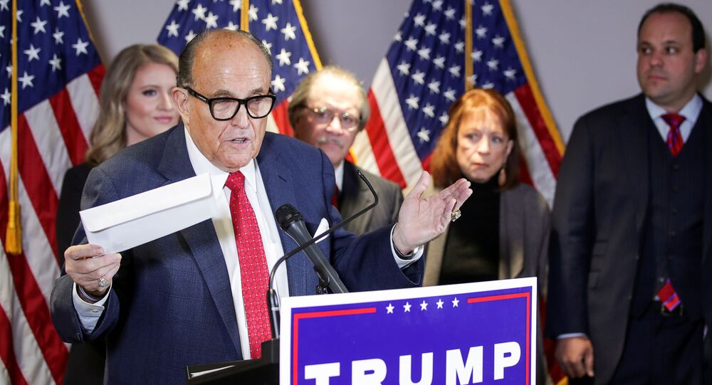 Former New York City Mayor Rudy Giuliani, personal attorney to US President Donald Trump, holds what he identifies as a replica mail-in ballot as he speaks about the 2020 US presidential election results during a news conference in Washington, 19 November 2020. REUTERS/Jonathan Ernst