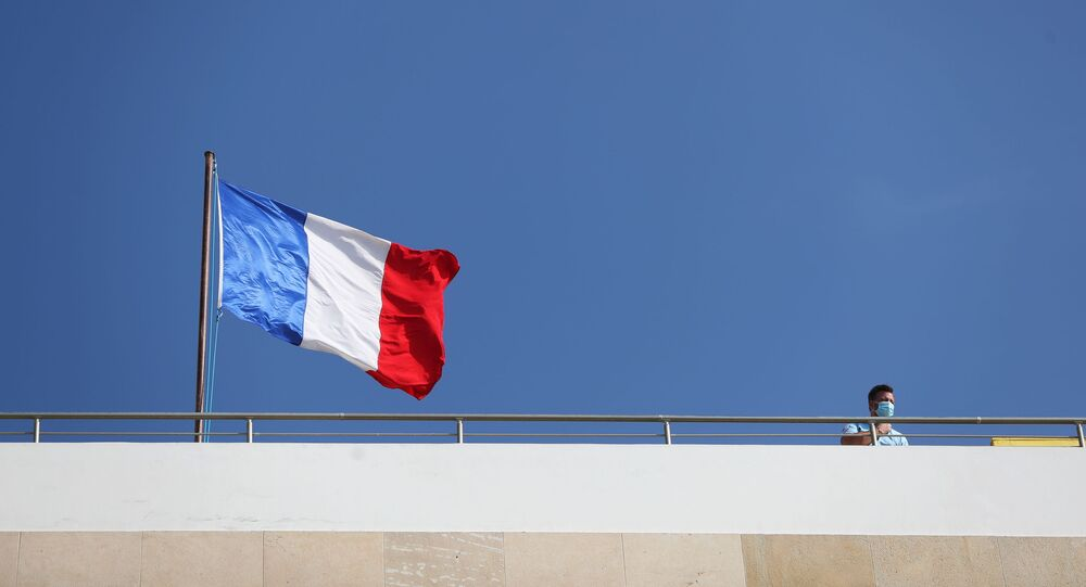 A man stands near a French flag as it flutters atop the roof of the French Embassy as protesters, including members of the Islamic Movement in Israel, demonstrate against the publications of a cartoon of Prophet Mohammad in France and French President Emmanuel Macron's comments, near the French Embassy in Tel Aviv, Israel October 29, 2020.