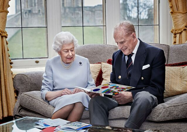 Britain's Queen Elizabeth and Prince Philip, Duke of Edinburgh look at their homemade wedding anniversary card, given to them by their great grandchildren Prince George, Princess Charlotte and Prince Louis, ahead of their 73rd wedding anniversary, in the Oak Room at Windsor Castle, Windsor, Britain November 17, 2020.