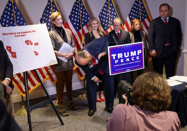 Former New York City Mayor Rudy Giuliani, personal attorney to U.S. President Donald Trump, jokingly looks underneath the podium after a reporter reacted to his claims and allegations about illegal voting fraud by asking Where is the FBI? as Giuliani held a news conference about the 2020 U.S. presidential election results at Republican National Committee headquarters in Washington, U.S., November 19, 2020.