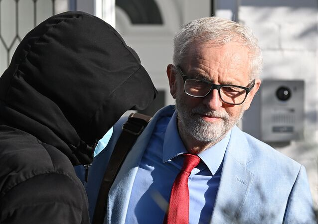 Jeremy Corbyn (R), former leader of Britain's Labour Party, reacts as he  leaves his home in north London on November 18, 2020. - The leader of Britain's main opposition Labour party on Wednesday refused to re-admit his predecessor Jeremy Corbyn to its parliamentary ranks as a row over anti-Semitism intensified.