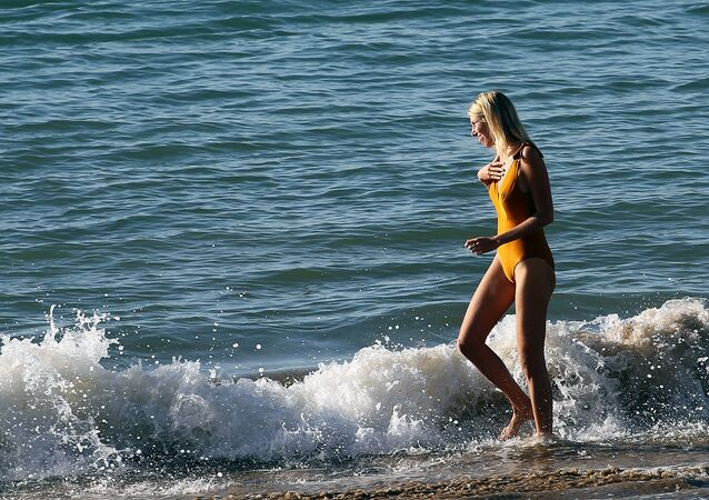 A woman paddles on the shores of the AtlanticOcean in Saint Jean de Luz, southwestern France, Wednesday, 18 November 2020.  France's health minister says the country is progressively getting back in control of its resurgent coronavirus epidemic but warns that it will quickly flare again if people start ignoring lockdown rules.