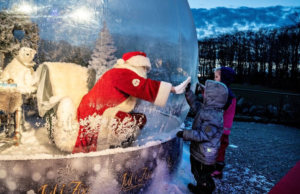 A person dressed as a Santa Claus meets with children while sitting in a Santa Claus bubble as he opens Christmas season at Aalborg Zoo, amid the coronavirus disease (COVID-19) outbreak, in Aalborg, Denmark, 13 November 2020.