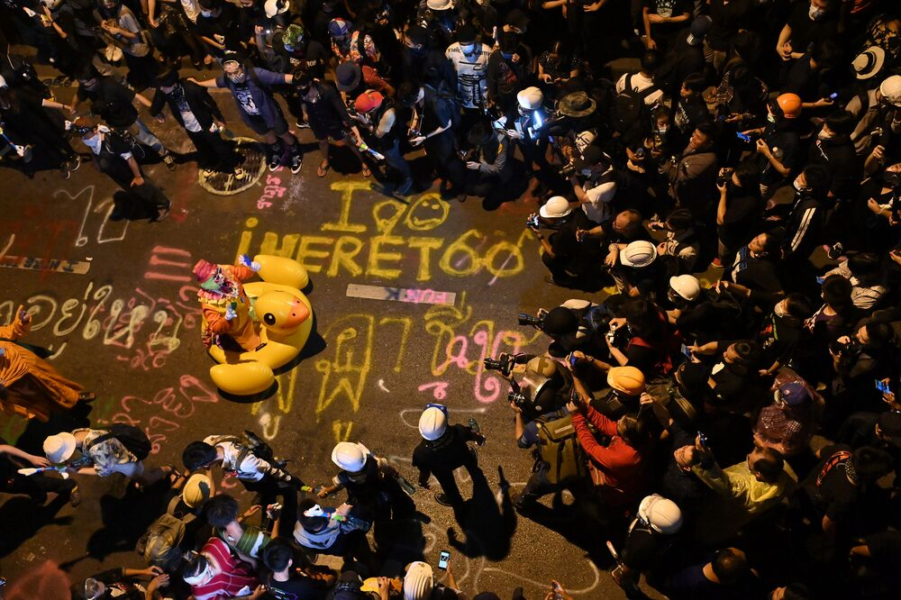 Members of the media take pictures of a clown on an inflatable oversized duck as pro-democracy protesters take part in an anti-government rally in Bangkok on 18 November 2020.