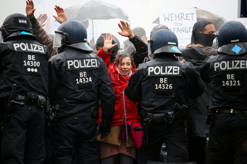 Demonstrators put up their hands in front of police officers during a protest against the government's coronavirus disease (COVID-19) restrictions, near the Brandenburger Gate in Berlin, 18 November 2020.